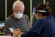 A man reads information after receiving the coronavirus vaccine at a vaccine center in Santa Barbara, Calif., Jan. 26, 2021.