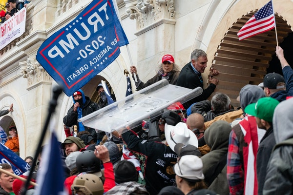Demonstrators steal a Metropolitan Police riot shield while attempting to enter the U.S. Capitol building in Washington, D.C., on Jan. 6, 2021. MUST C