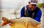 Justin Watkins with a common carp, regarded by the DNR as perhaps the most damaging invasive species in state waters.