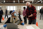 Gov. Tim Walz, right, talked with Jevetta Steele who was checking in people with COVID-19 vaccine appointments on Thursday at the Earle Brown Heritage