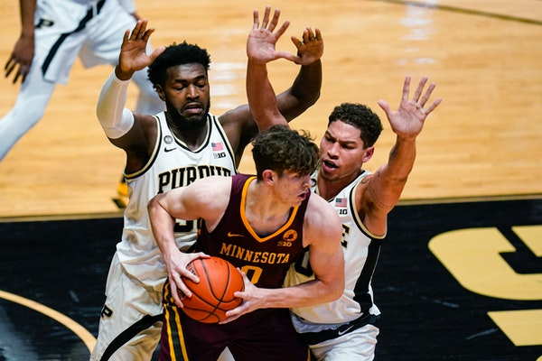 Minnesota center Liam Robbins is trapped between Purdue forward Trevion Williams and forward Mason Gillis on Saturday.