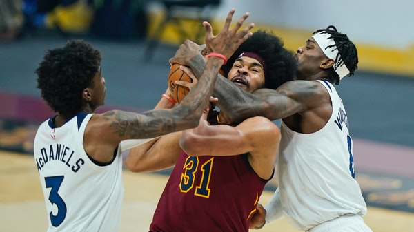 The Wolves' Jarred Vanderbilt, right, fouled the Cavaliers' Jarrett Allen as Jaden McDaniels defended in the first half Monday.