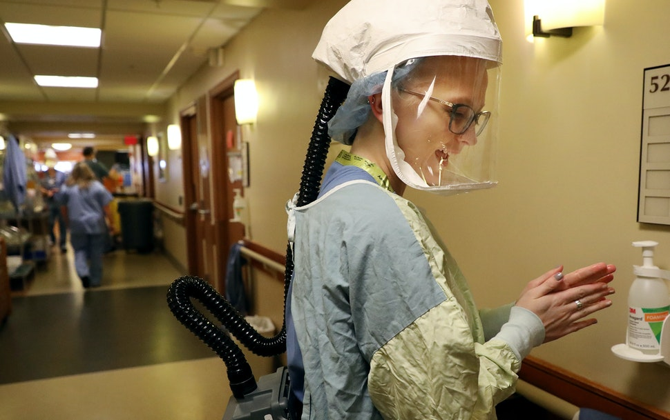 After donning personal protective equipment RN Sarah Neva sanitizes her hands before going in to check on a COVID-19 patient on the fifth floor at Bet