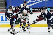 Minnesota Wild right wing Gerald Mayhew, front center, fights for control of the puck with, from left, Colorado Avalanche defensemen Cale Makar and Bo