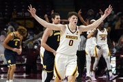 Liam Robbins celebrates a three-point shot during a win against Michigan on Jan. 16. The Gophers had their next game postponed, derailing momentum.