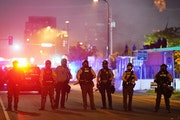 Police stood guard after using tear gas to clear a group of hundreds of protesters that had gathered near the Minneapolis Police 5th Precinct in the h