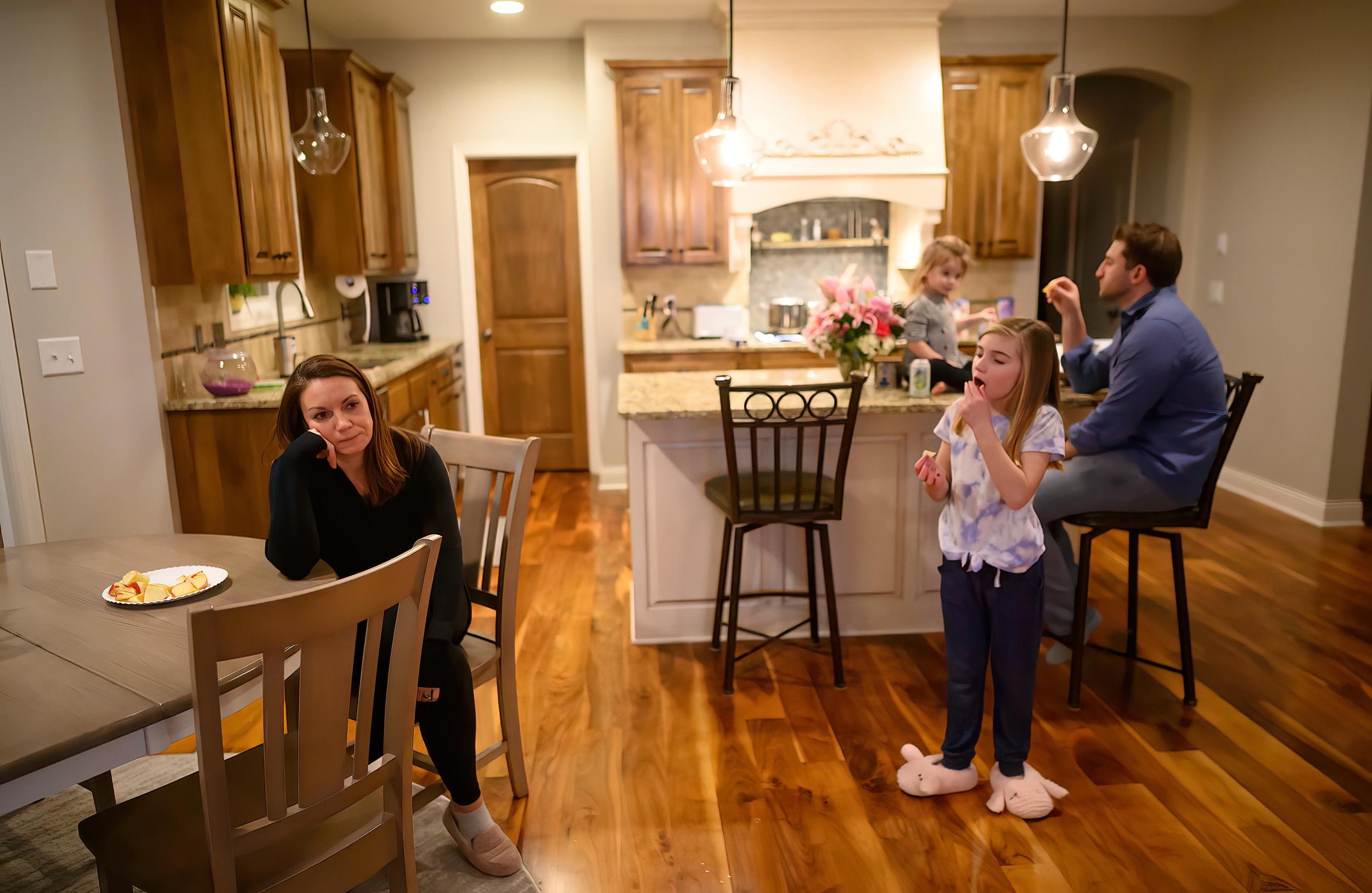 Holly Vilione looked on as her daughters Nora, 2, Mya, 8 and husband, Chris Vilione, snacked in the kitchen a few hours after Holly returned from another difficult day working in the ICU.