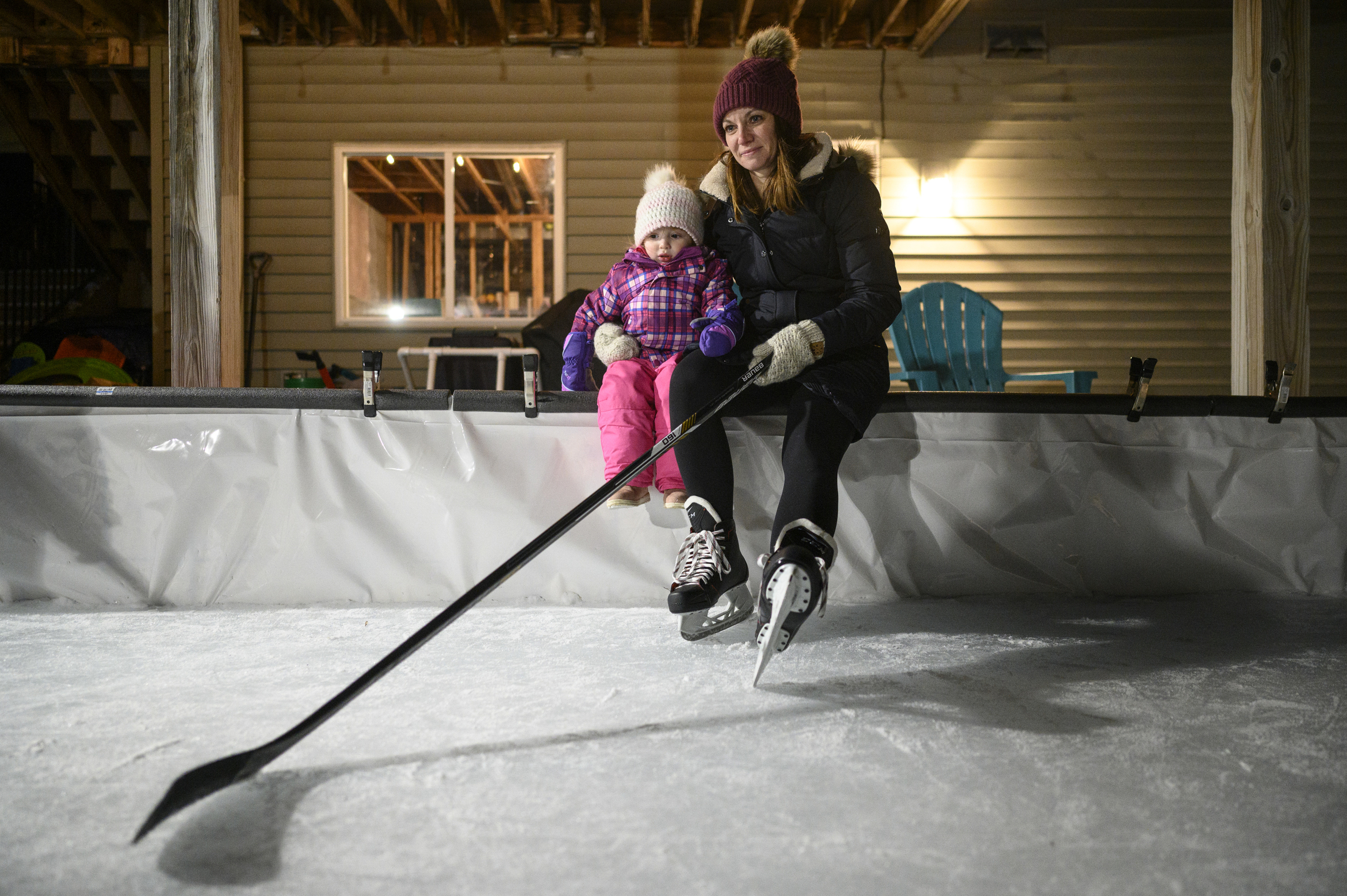 Holly Vilione sat with her 2-year old daughter, Nora, while taking a break from playing some backyard hockey with her kids and nieces in late January.