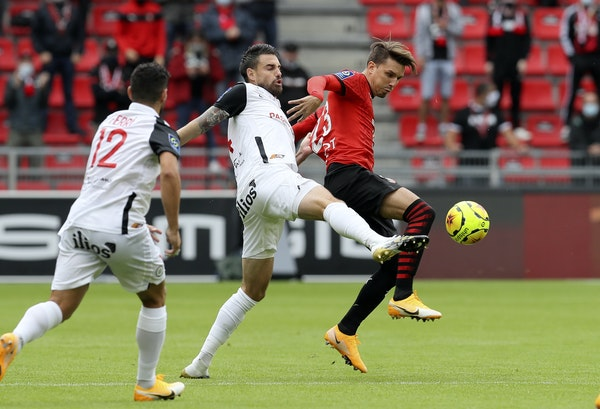 Stade Rennais' Adrien Hunou, right, challenged for the ball with Montpellier's Damien Le Tallec, center, in a League One match on Aug. 29, 2020 at