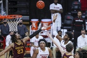 Rutgers center Myles Johnson shoots over the Gophers' Brandon Johnson and Liam Robbins Thursday night in New Jersey.