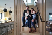 Phil and Jayme Hanson and their children Vera, 4, and Otis, 2, sat on the stairs inside their remodeled home. They returned to it from living in Denma