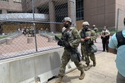 Armed members of the Minnesota National Guard are shown leaving the Hennepin County Public Safety Facility in downtown Minneapolis, on Thursday, June