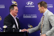 Minnesota Vikings new quarterback Kirk Cousins, right, is welcomed to the podium by head coach Mike Zimmer after signing in 2018.