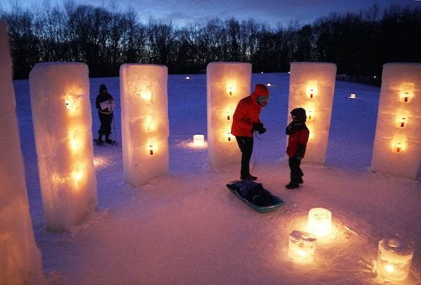 Gregg Lind checked on his son Galen Beil, 8, as they and Melissa Arbuckle, left, looked over the Ice Henge sculpture during the Luminary Loppet Friday