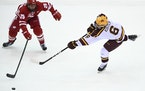 Gophers defenseman Mike Koster tried to get a shot around Wisconsin's Dominick Mersch during a game at Mariucci Arena two weeks ago.