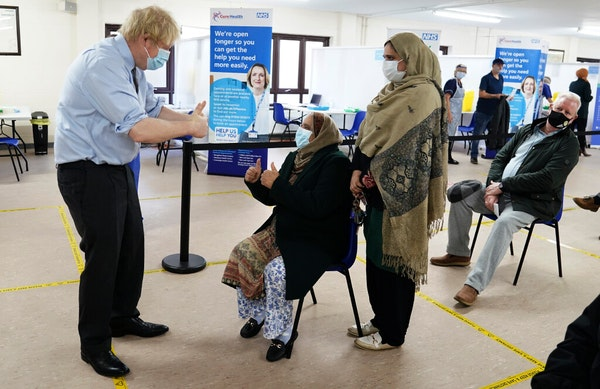Britain's Prime Minister Boris Johnson gives a thumbs up to patients after they received thevaccineas he visits aCOVID-19 vaccination centre i