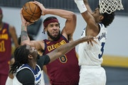 Cleveland Cavaliers' JaVale McGee, center, drives to the basket against Minnesota Timberwolves' Naz Reid, left, and Jaden McDaniels , right.