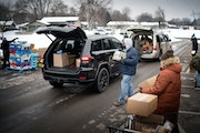 Kenny Smith and Jan Sautler loaded food into trunks and tailgates during the distribution.  Over 300 cars lined up around the block by New Creation Lu