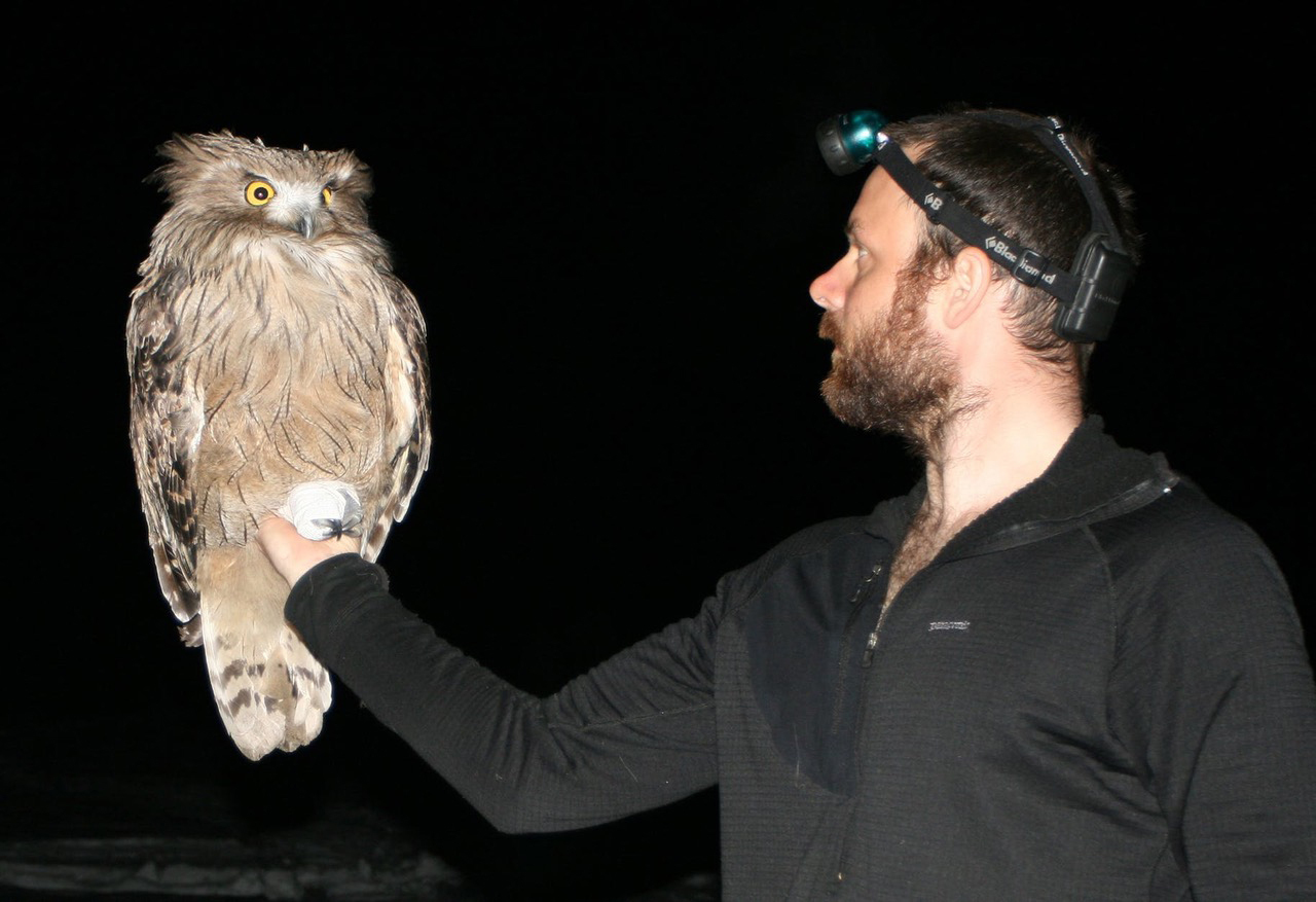 Jonathan Slaght and a fish owl.