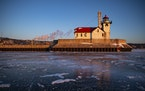 The Duluth Harbor south breakwater outer light was was illuminated by the rising sun over a frozen Lake Superior on Tuesday.