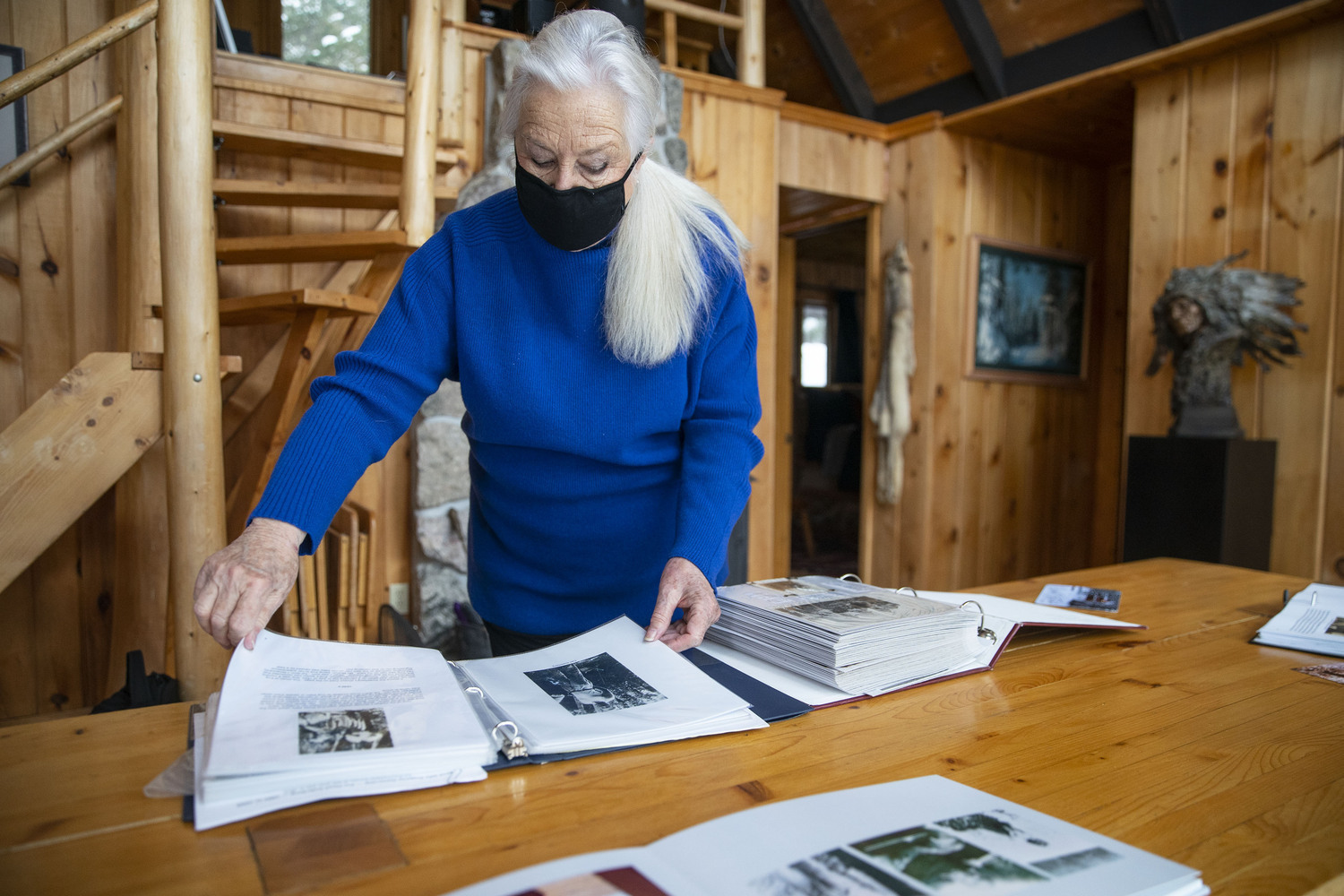 At her cabin, Leddy looked through photos books stuffed with images of their deep Gunflint Trail history.
