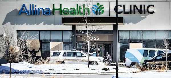 A worker placed sheets of plywood Wednesday over windows that were shot out Tuesday at Allina Health clinic in Buffalo. One woman was killed and four