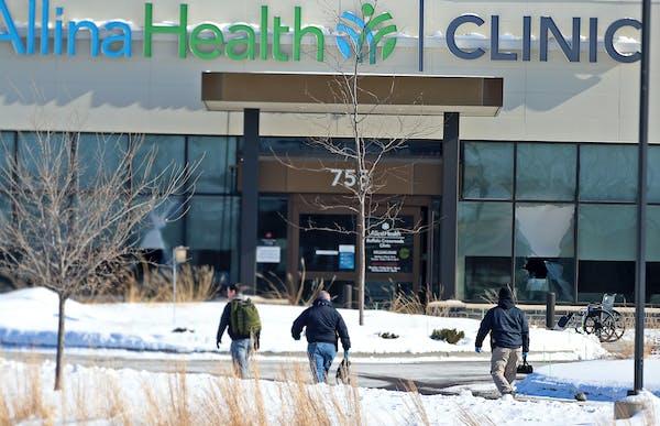 Law enforcement personnel walk toward the Allina Health clinic on Tuesday in Buffalo, Minn.