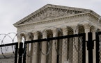 The Supreme Court is visible behind razor wire covered fencing in Washington, on Feb. 10, during the second impeachment trial of former President Dona