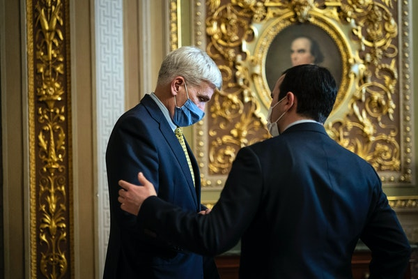 Sen. Bill Cassidy, R-La., talks with a staff member on the fourth day of the Senate impeachment trial of former President Donald Trump on Capitol Hill