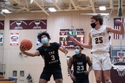 South St. Paul Packers Keon Moore (3) grabbed a rebound past Mahtomedi Zephyrs Will Underwood (25)