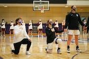 Ruth Sinn, returning for her 16th season as Tommies womenÕs basketball head coach, knelt alongside her St. Thomas team before that start of a game ag