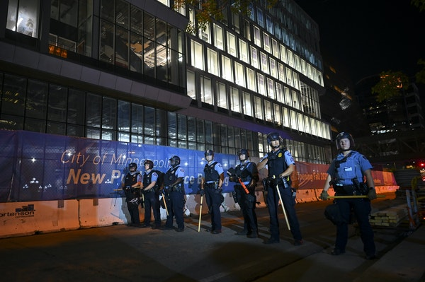 Minneapolis Police officers formed a line as a makeshift barricade erected by protesters earlier was removed along South Fourth Avenue.     ]aaron.lav