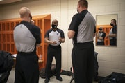 Crew Chief Lamarr Sullivan went over the plan for officiating a game between Anoka and Osseo with his colleagues Denny Misener, left, and Kevin Markli
