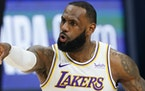 Los Angeles Lakers forward LeBron James gestures to teammates during the second half of an NBA basketball game against the Denver Nuggets on Sunday, F