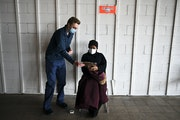 Intern Jens Mellby set up a second appointment for a vaccination shot with Teretha Glass, 72, of St. Paul, after Glass received her first dose of the