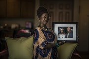 Portrait of Magdalene Menyongar at home holding a photo of her mom Youbsrboh Menyongar and her twin brother David S Menyongar February 15, 2021 in Map