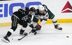 Los Angeles Kings defenseman Tobias Bjornfot, left, and Minnesota Wild left wing Jordan Greenway vie for the puck during the first period