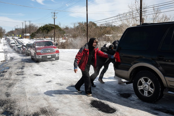 People help a motorist up a snow and ice-covered road on Tuesday, Feb. 16, 2021, in Austin, Texas. As a winter storm forced the Texas' power grid to