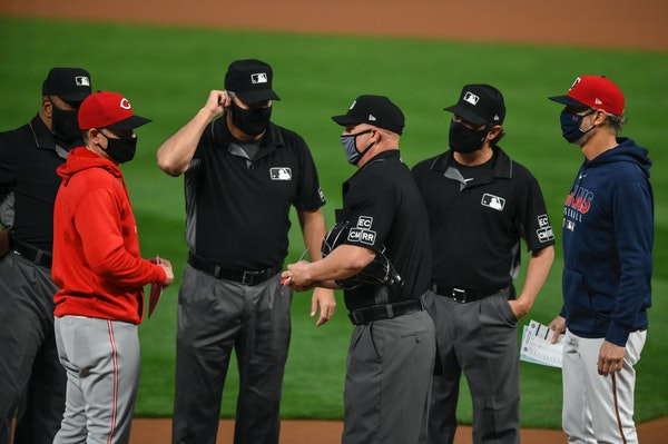 Mike Bell, right, exchange lineup cards with the umpires and his brother, Reds manager David Bell, before a game last season at Target Field.