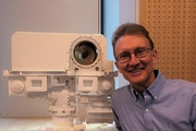 Roger Wiens stands next to a SuperCam on a model of NASA's Perseverance rover. (Photo courtesy Roger Wiens)