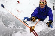 Lou Renner search for the final spot to drive in his ice axe as he topped out on an ice route at Robinson Park.
