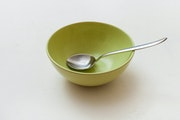 green bowl with spoon on white plastering plate