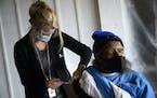 United Family Medicine nurse Julie Sharp vaccinated Roosevelt Austin Jr., 57, against COVID-19 earlier this month.   (AARON LAVINSKY • aaron.lavinsk