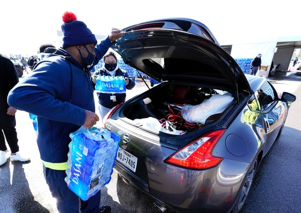 Water is loaded into the trunk of a car at a City of Houston water distribution site Friday, Feb. 19, 2021, in Houston. The drive-thru stadium locatio