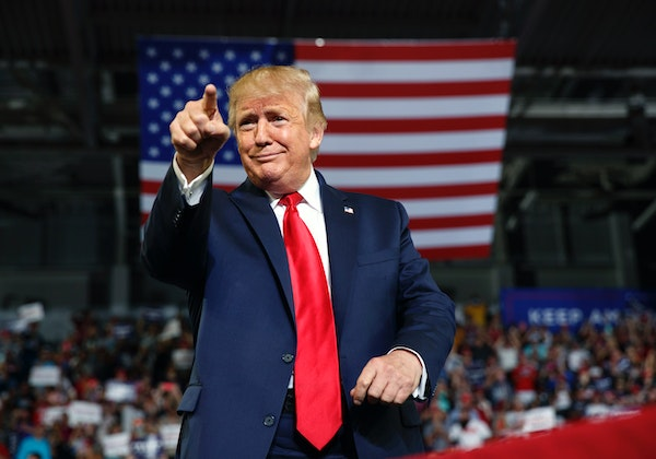 Then-President Donald Trump gestures to the crowd as he arrives to speak at a July 2019 campaign rally at Williams Arena in Greenville, N.C.