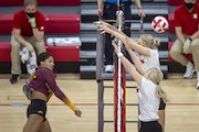Minnesota's Taylor Landfair (12) attempts a kill against Nebraska's Lauren Stivrins (26) and Nicklin Hames (1) during the first set of a college volle