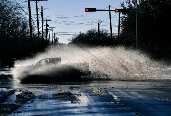 A pickup sends a wake of snow melt high into the air as the driver plows through a large puddle at Barrow and South 11th streets intersection in Abile