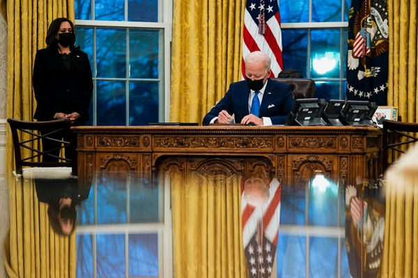 President Joe Biden signs several executive orders directing immigration actions for his administration as Vice President Kamala Harris looks on in th