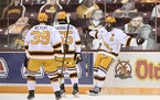 Gophers forward Cullen Munson (13) celebrated with Ben Meyers (39) and Matt Staudacher (55) after Munson's first-period goal against Michigan State
