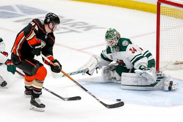 Minnesota Wild goalie Kaapo Kahkonen (34) defends as Anaheim Ducks forward Max Jones (49) shoots during the third period of an NHL hockey game Saturda
